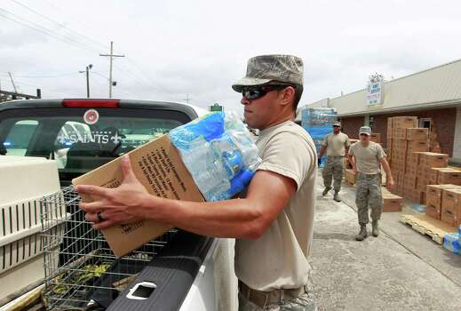 Louisiana Air National Guard Kevin Bussard works to distribute water and prepackaged food to victims of Hurricane Isaac Friday, Aug. 31, 2012, in Belle Chasse, La. Isaac sloshed north into the central U.S. on Friday after flooding stretches of Louisiana and Mississippi and knocking out power, leaving entire water-logged neighborhoods without lights, air conditioning or clean water. (AP Photo/John Bazemore) Photo: John Bazemore, Associated Press / AP