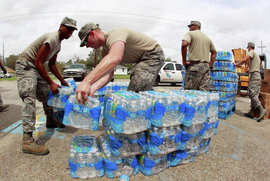 Members of the Louisiana Air National Guard work to distribute water and prepackaged food to victims of Hurricane Isaac Friday, Aug. 31, 2012, in Belle Chasse, La. Isaac sloshed north into the central U.S. on Friday after flooding stretches of Louisiana and Mississippi and knocking out power, leaving entire water-logged neighborhoods without lights, air conditioning or clean water. (AP Photo/John Bazemore) Photo: John Bazemore, Associated Press / AP