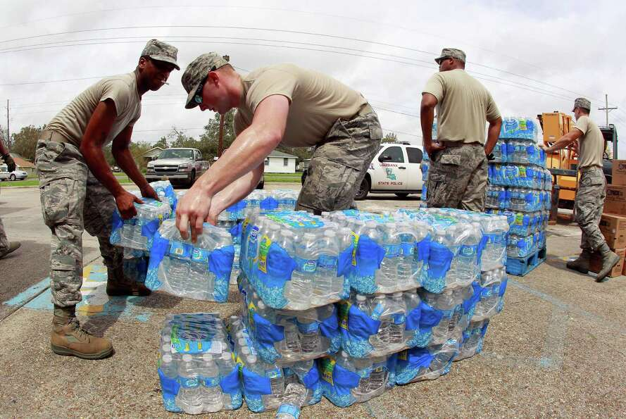 Members of the Louisiana Air National Guard work to distribute water and prepackaged food to victims