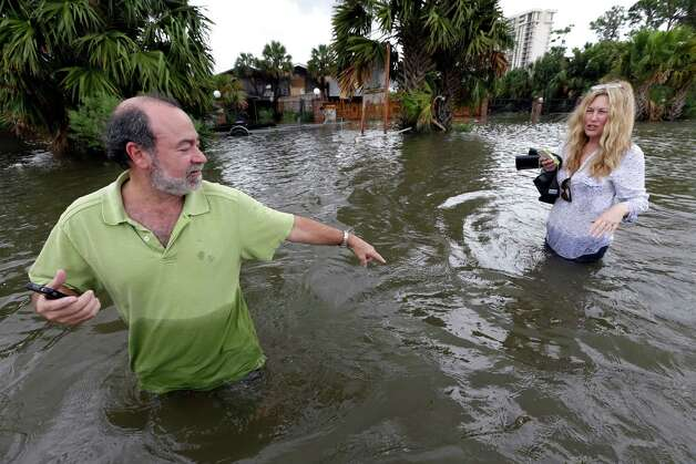 Kenny Melkin, left, helps his wife Becky navigate through floodwaters from Hurricane Isaac as they make their way to see their flooded home in the West End Park neighborhood along Lake Pontchartrain, Friday, Aug. 31, 2012 in New Orleans. Isaac is now a tropical depression and the center was on track to cross Arkansas on Friday and southern Missouri on Friday night, spreading rain as it goes. (AP Photo/David J. Phillip) Photo: David J. Phillip, Associated Press / AP