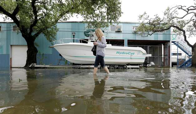 Becky Melkin wades through floodwaters from Hurricane Isaac as she makes her way back to her flooded home in the West End Park neighborhood along Lake Pontchartrain, Friday, Aug. 31, 2012 in New Orleans. Isaac is now a tropical depression and the center was on track to cross Arkansas on Friday and southern Missouri on Friday night, spreading rain as it goes. (AP Photo/David J. Phillip) Photo: David J. Phillip, Associated Press / AP