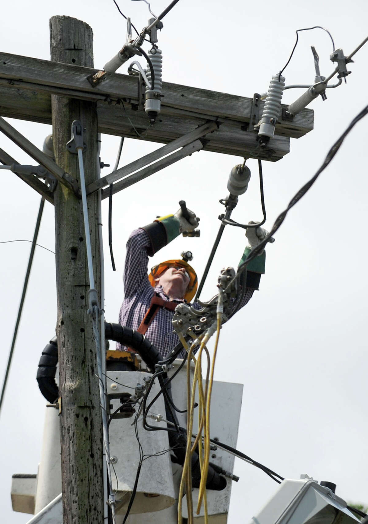 CL&P worker Art Sikora of Southbury, works to repair service on Candlewood Lake Road in Brookfield Friday last summer.