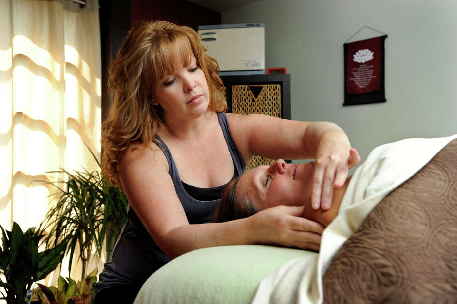 Laura Ahern, left, a licensed massage therapist and owner of Green Blessings Center in Southbury, gives a massage to Sharon Martovich, of Southbury on Friday, Aug. 31, 2012. Martovich  is the owner of Eat, Play, Live. Photo: Carol Kaliff / The News-Times
