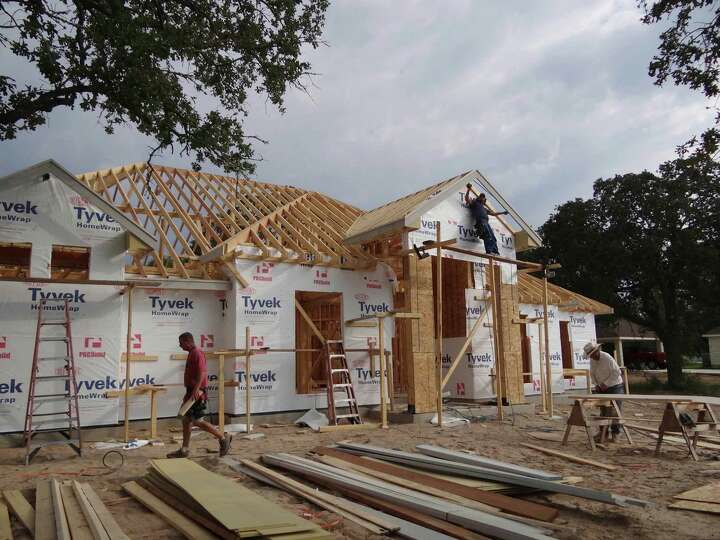 Workers labor on a DC Builders home, one of several being built in the Abrego Lake subdivision in Fl