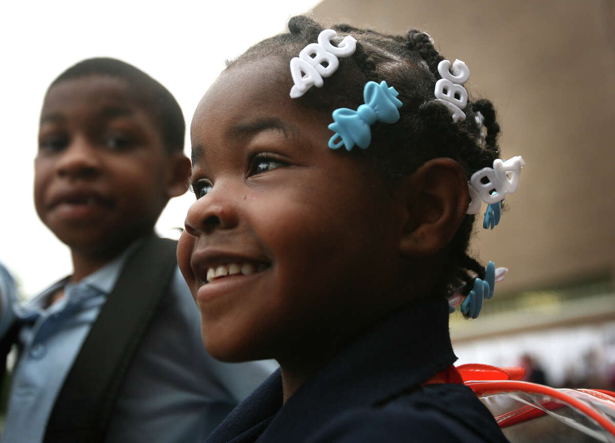 With her brother Nemo Wlliams, 7, left, Zy-maria Williams, 5, arrives for her first day of kindergarten at Curiale School in Bridgeport on Tuesday, August 28, 2012.