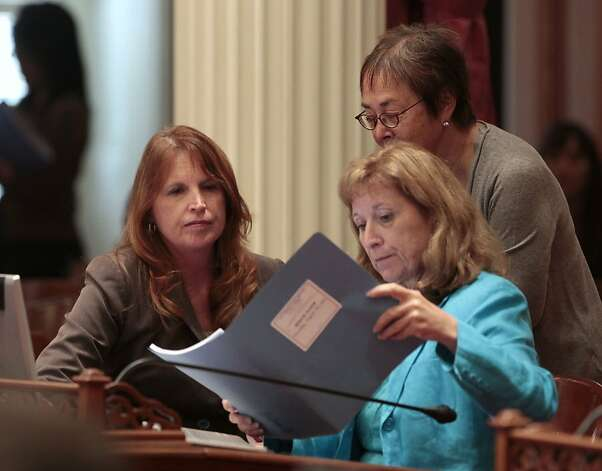 Democratic State Senators Noreen Evans, of Santa Rosa, left, Ellen Corbett, of San Leandro, right, and Carol Liu, of Pasadena, standing look over some papers at the Capitol in Sacramento, Calif., Thursday, Aug. 30, 2012. Lawmakers are pouring through hundreds of bill to finish all Legislative business by their midnight Friday deadline.(AP Photo/Rich Pedroncelli) Photo: Rich Pedroncelli, Associated Press