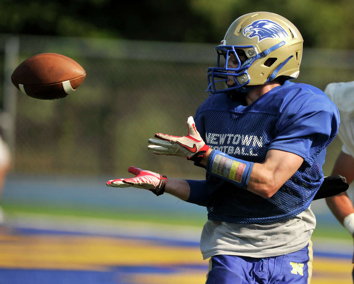 Newtown's Dan Hebert catches a ball and runs it in for a touchdown during a scrimmage against Seymour at Newtown High School on Friday, Aug. 31, 2012.