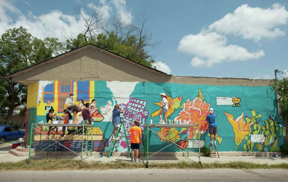 Artists paint a mural on an old grocery building, Saturday, Aug. 25, 2012, at the corner of South Picoso and San Carlos streets in San Antonio. Photo: Darren Abate, For The Express-News