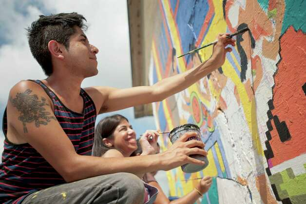 Eddie Chavez, foreground, and Deborah Rubinstein, paint a mural on an old grocery building, Saturday, Aug. 25, 2012, at the corner of South Picoso and San Carlos streets in San Antonio. Photo: Darren Abate, For The Express-News
