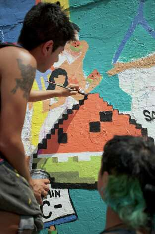 Eddie Chavez, left, and Michael Cuevas, paint a mural on an old grocery building, Saturday, Aug. 25, 2012, at the corner of South Picoso and San Carlos streets in San Antonio. Photo: Darren Abate, For The Express-News