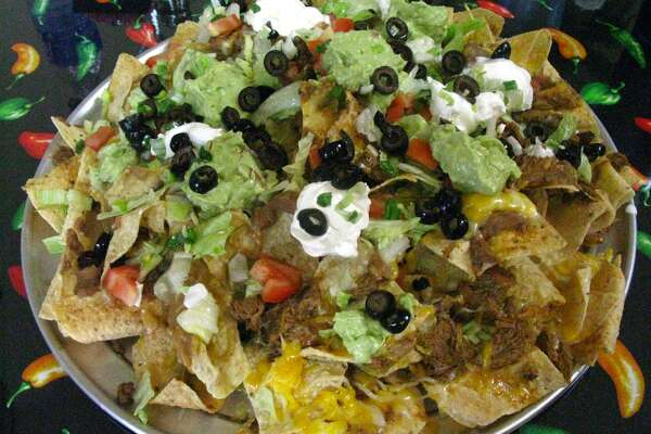 "Extreme Nachos at Marianito's Extreme Tex-Mex Grill are served on a 16-inch pizza pie pan. The restaurant at 2102 Bandera Road was featured on Food Network's ""Outrageous Food"" in 2010.  (JENNIFER MCINNIS / SAN ANTONIO EXPRESS-NEWS)"