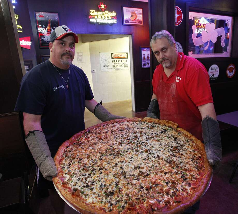 "Brothers, from the left, Art and Brian Lujan show off one of the famous 42-inch pizzas at Big Lou's Pizza. ""Man vs Food"" host Adam Richman visited the establishment in 2009."
