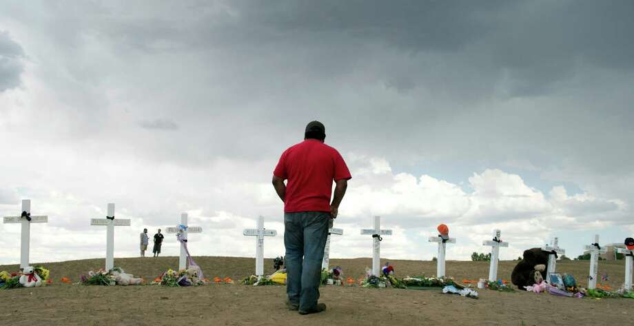 A man pauses at a row of crosses that were erected in Aurora, Colo., as a memorial to the victims who were killed in the mass shooting at the Century 16 movie theater in July. Photo: DON EMMERT / AFP ImageForum