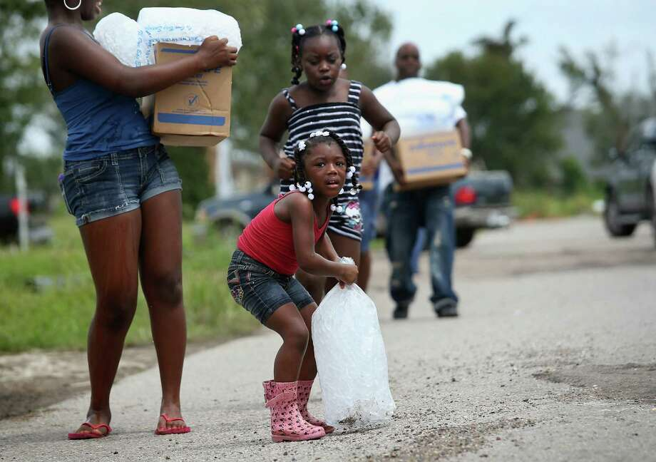 A family carries bags of ice and boxes of food from an aid distribution center for victims of this week's Hurricane Isaac in New Orleans. Photo: John Moore, Getty Images / 2012 Getty Images