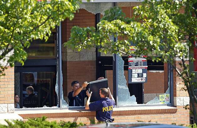 Police officers remove a computer from a Pathmark supermarket in Old Bridge, New Jersey. The store's front windows were shattered by gunfire. Photo: Rich Schultz, Associated Press