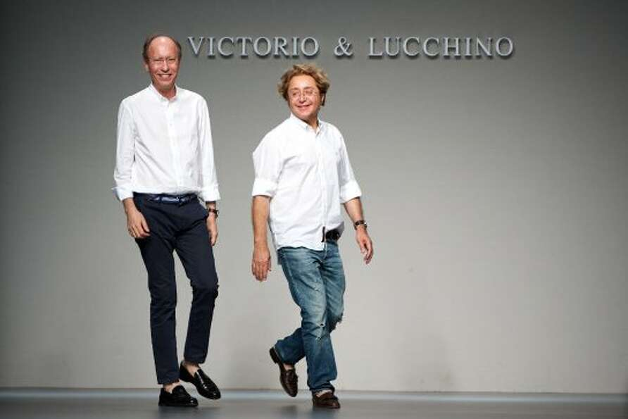 Spanish fashion designers Jose Victor Caro (R) and Jose Luis Medina (L) walk the runway at the end o