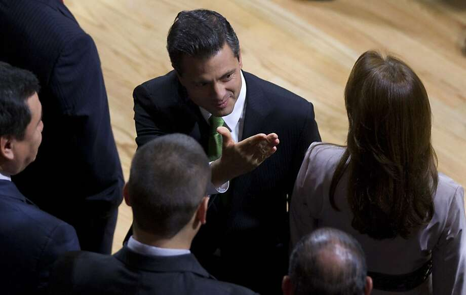 Mexico's President-elect Enrique Pena Nieto, center, of the Institutional Revolutionary Party (PRI), gestures as his wife Angelica Rivera stands at right during a ceremony at the Federal Electoral Tribunal (TRIFE) in Mexico City, Friday, Aug. 31, 2012. The TRIFE declared Pena Nieto won the majority of votes in last July's presidential election and he will be sworn-in to office on Dec. 1. (AP Photo/Eduardo Verdugo) Photo: Eduardo Verdugo, Associated Press