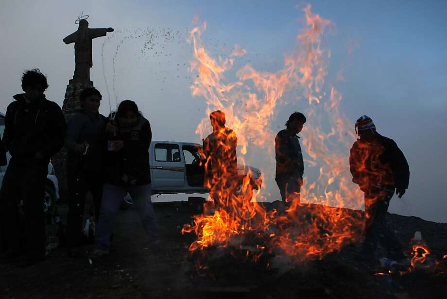 "In this Aug. 15, 2012 photo, people burn offerings to the ""Pachamama,"" or Mother Earth, on El Cumbre mountain, considered sacred, near a statue of Jesus Christ on the outskirts of La Paz, Bolivia. During the month of August, people gather on sacred mountains to make offerings and ask for wealth to Mother Earth.  According to local agrarian tradition, Mother Earth awakes hungry and thirsty in August and needs offerings of food and drink in order for her to be fertile and yield abundant crops. (AP Photo/Juan Karita) Photo: Juan Karita, Associated Press"