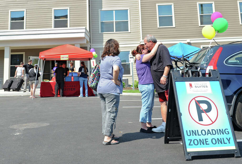 From left, Meryl Zucker from Long Island watches her daughter Ariana giver her giver her dad Stuart a tearful goodbye in the parking lot as Schenectady County Community College (SCCC) students move into the brand new College Suites at Washington Square Friday, Aug. 31, 2012 in Schenectady, N.Y. (Lori Van Buren / Times Union) Photo: Lori Van Buren