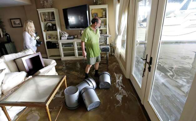 Kenny Melkin, right, and his wife Becky return home to see the flood damage caused by Isaac in the West End Park neighborhood along Lake Pontchartrain, Friday, Aug. 31, 2012 in New Orleans. Isaac crawled into the central U.S. on Friday, leaving behind a soggy mess in Louisiana.  It will be a few days before the water recedes and people in flooded areas can return home. New Orleans itself was spared, thanks in large part to a levee system fortified after Katrina devastated the Gulf Coast in 2005. Photo: David J. Phillip, Associated Press / AP