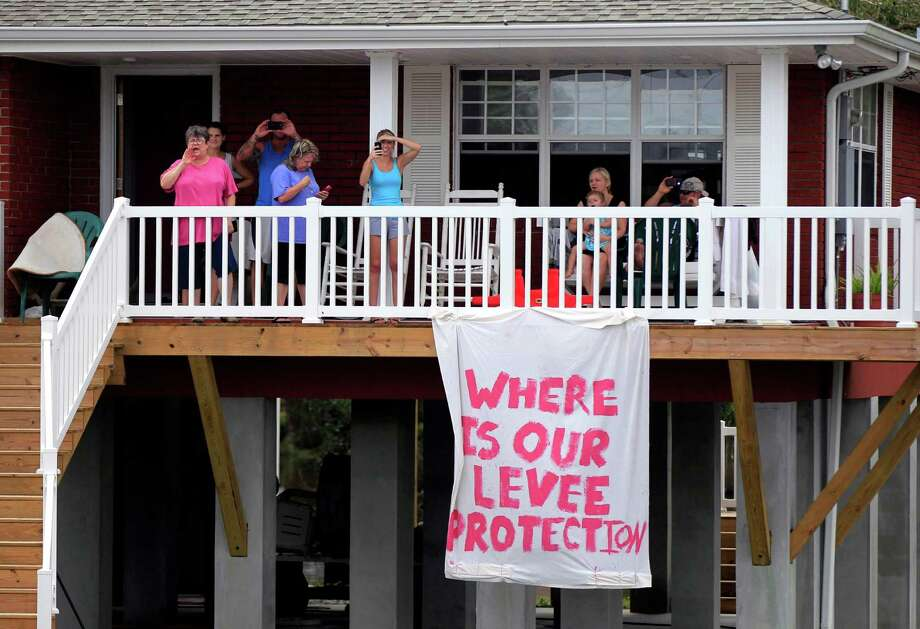 People shout from a porch amidst floodwaters from Isaac as Republican presidential candidate Mitt Romney's motorcade passes in the through Lafitte, La., Friday, Aug. 31, 2012. Photo: Gerald Herbert, Associated Press / AP