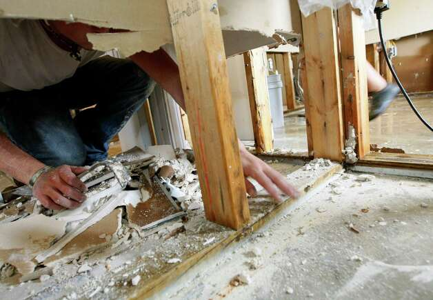 Justin Gambill collects wet and torn sheet rock cut from a closet in the home of Sammy and Terri Vance, Friday, Aug. 31, 2012, in  Bay St. Louis, Miss. The house took on almost two feet of water from Isaac. Vance, family members and friends removed personal possessions and appliances as they began the long road to recovery from the hurricane. Photo: Rogelio V. Solis, Associated Press / AP