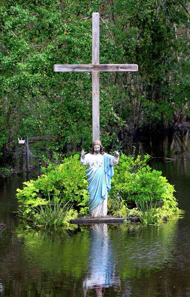 A statue of Jesus and a cross are inundated by floodwaters in the aftermath of Isaac in Lafitte, La.