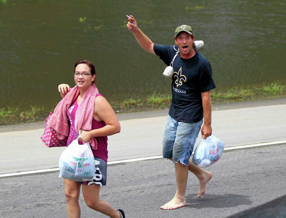People walk with possessions on their way out of floodwaters from Isaac as  Republican presidential candidate Mitt Romney's motorcade passes in the aftermath of the storm in Lafitte, La., Friday, Aug. 31, 2012. Isaac is now a tropical depression, with the center on track to cross Arkansas on Friday and southern Missouri on Friday night, spreading rain through the regions. Photo: Gerald Herbert, Associated Press / AP