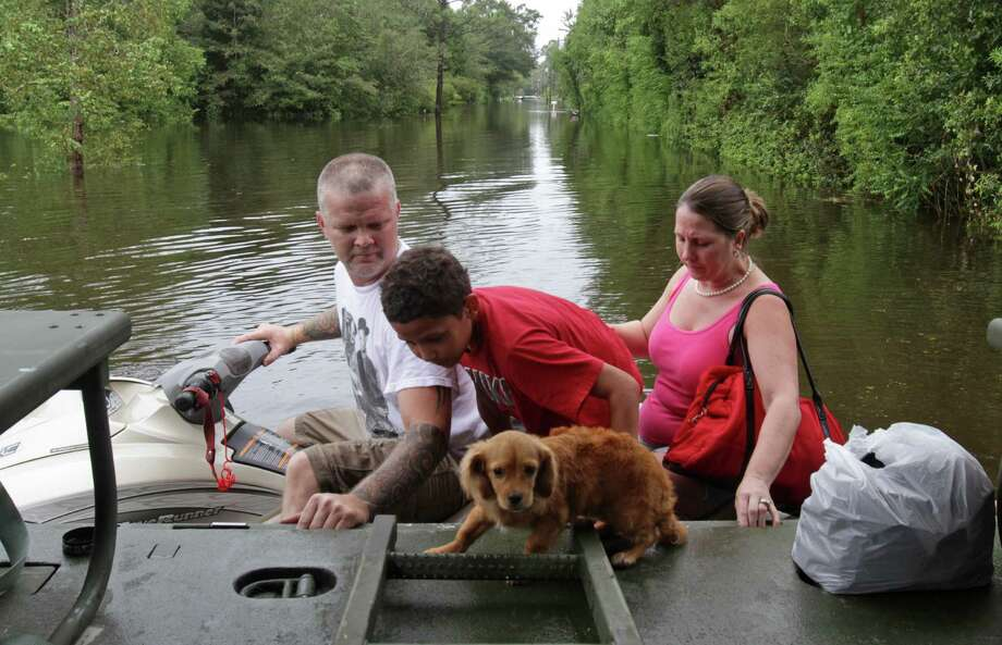 Jeff Delaughter, left, uses a personal water craft to deliver Sabastien Ward, 10, his dog, Stewie, and mother, Winter, to an Army National Guard truck in the Helena community in Jackson County, Miss. on Friday Aug. 31, 2012 after rain from Hurricane Isaac caused flooding in the area. Photo: JOHN FITZHUGH, Associated Press / SUN HERALD