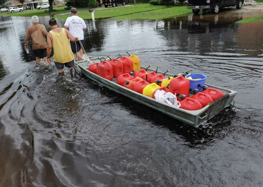 Neighbors David Nelson, left, Dennis Rodrigue, center, and Daniel Tally pull a boat full of gas, Friday Aug. 31, 2012, to run generators at five home in the LaPlace neighborhood of River Forest. Residents of LaPlace started cleaning up after flooding caused by Hurricane Isaac. Photo: Arthur D. Lauck, Associated Press / The Advocate