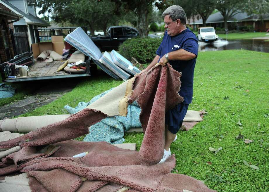 Mitch Smith pulls wet carpet from his home in LaPlace, La., Friday Aug. 31, 2012 that was flooded by Hurricane Isaac. Residents across the area began the long process of cleaning up after flooding caused by Hurricane Isaac. Photo: Arthur D. Lauck, Associated Press / The Advocate