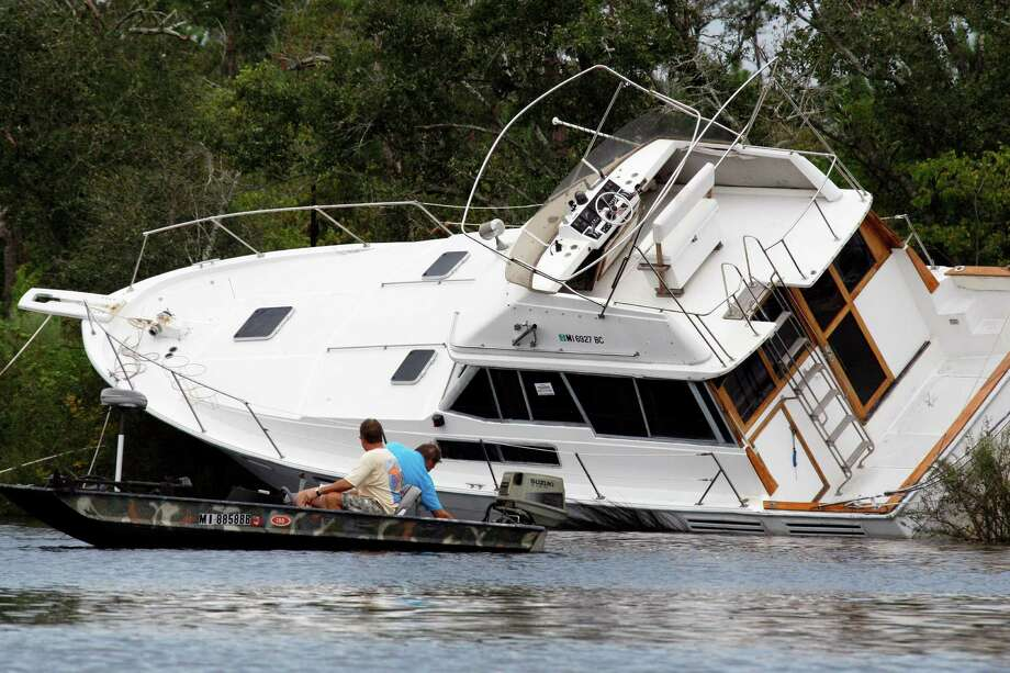 Several men try to free this grounded yacht on Twin Lake, near Diamondhead, Miss., Friday, Aug. 31, 2012. Area residents often anchor their boats during storms in lake. Strong winds and high waters caused by Isaac forced the grounding. A house boat was demolished nearby. Photo: Rogelio V. Solis, Associated Press / AP