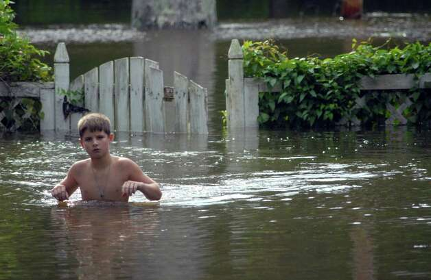 Tyler Brown wades through the floodwaters from Magee's Creek at a relative's house in Tylertown, Miss., on Thursday, Aug. 30, 2012. Isaac blew ashore as a hurricane Tuesday night, soaking south Louisiana and Mississippi. It was downgraded to a tropical storm Wednesday and to a tropical depression Thursday. High winds damaged buildings Thursday in Ocean Springs and Pascagoula. Photo: Matt Williamson, Associated Press / The Enterprise-Journal