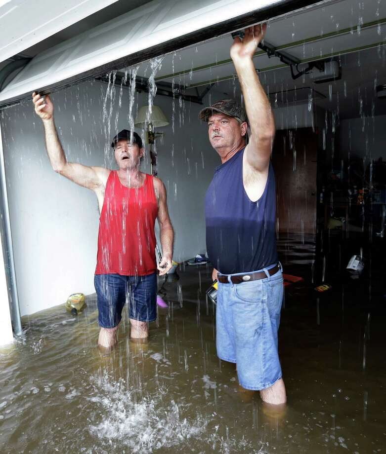Frank Story, left, reacts when he is hit by cool water as he helps friend Christopher Tabb, right, open the garage door of his flooded home, Friday, Aug. 31, 2012, in LaPlace, La.  Isaac crawled into the central U.S. on Friday, leaving behind a soggy mess in Louisiana.  It will be a few days before the water recedes and people in flooded areas can return home. New Orleans itself was spared, thanks in large part to a levee system fortified after Katrina devastated the Gulf Coast in 2005. Photo: Eric Gay, Associated Press / AP