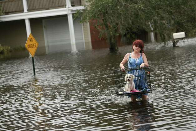 Jill Frisard carries her friend's dog, Buddy, from her flooded home in Slidell, La., Aug. 31, 2012. On Monday, President Barack Obama will visit the Gulf Coast to tour the damage from Hurricane Isaac and meet with officials about the recovery efforts. Photo: MICHAEL APPLETON, NYT / NYTNS