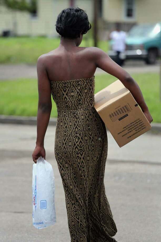 A woman carries food and ice from an aid distribution center for victims of Hurricane Isaac on August 31, 2012 in New Orleans, Louisiana. The center was one of three in New Orleans operated by the Louisiana National Guard, which handed out bags of ice, boxes of food and tarps to residents, many of whom still have no electricity due to the storm. Photo: John Moore, Getty Images / 2012 Getty Images
