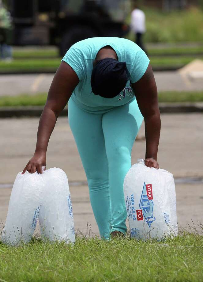 A woman pauses while carrying bags ice from an aid distribution center for victims of Hurricane Isaac on August 31, 2012 in New Orleans, Louisiana. The center was one of three in New Orleans operated by the Louisiana National Guard, which handed out bags of ice, boxes of food and tarps to residents, many of whom still have no electricity due to the storm. Photo: John Moore, Getty Images / 2012 Getty Images