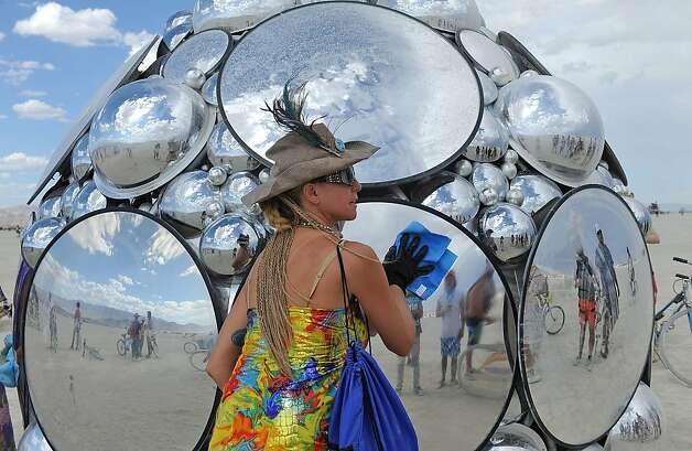 Artist Kirsten Berg cleans her art work on the playa at Burning Man on the Black Rock Desert near Gerlach, Nev. on Friday Aug. 31, 2012. (AP Photo/Reno Gazette-Journal, Andy Barron) Photo: Andy Barron, Associated Press