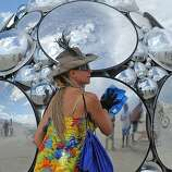 Artist Kirsten Berg cleans her art work on the playa at Burning Man on the Black Rock Desert near Gerlach, Nev. on Friday Aug. 31, 2012. (AP Photo/Reno Gazette-Journal, Andy Barron)