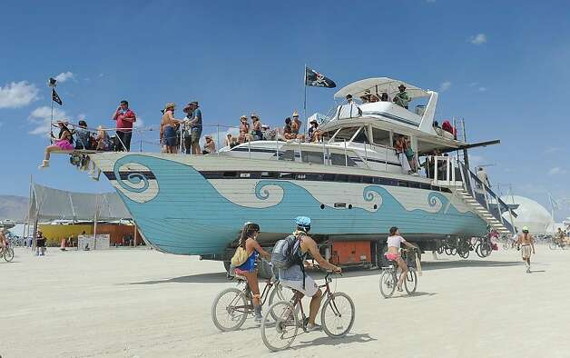 An old wooden yacht art car rolls through the playa at Burning Man on the Black Rock Desert near Gerlach, Nev. on Friday Aug. 31, 2012 on Friday Aug. 31, 2012. (AP Photo/Reno Gazette-Journal, Andy Barron) Photo: Andy Barron, Associated Press