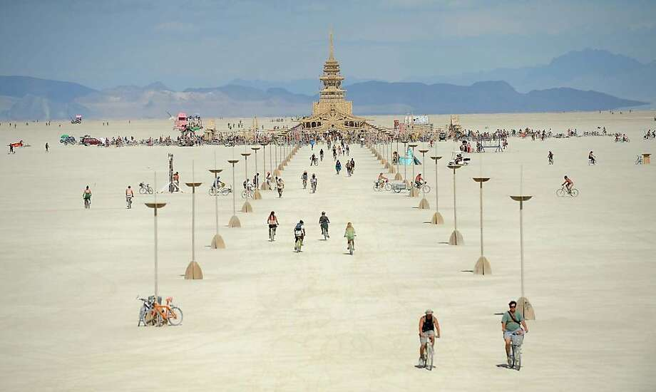 People walk toward the temple at Burning Man near Gerlach, Nev., on the Black Rock Desert on Friday Aug. 31, 2012. (AP Photo/The Reno Gazette-Journal, Andy Barron) Photo: Andy Barron, Associated Press