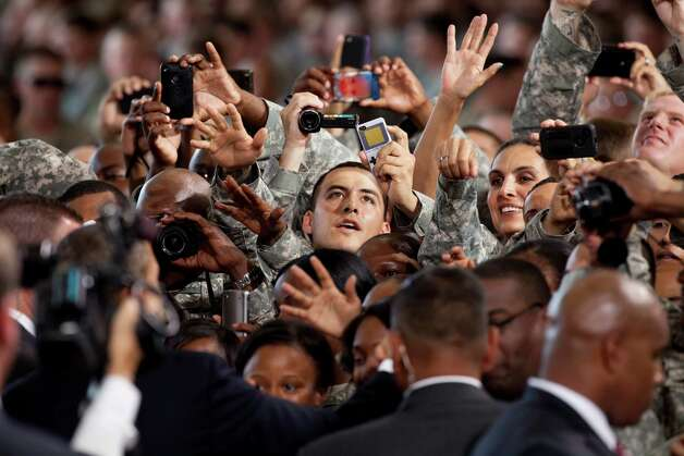 Fort Bliss soldiers try to meet and photograph President Barack Obama, left, after addressing them at Fort Bliss Military Installation on August 31, 2012. The president met privately with service members and their families and 