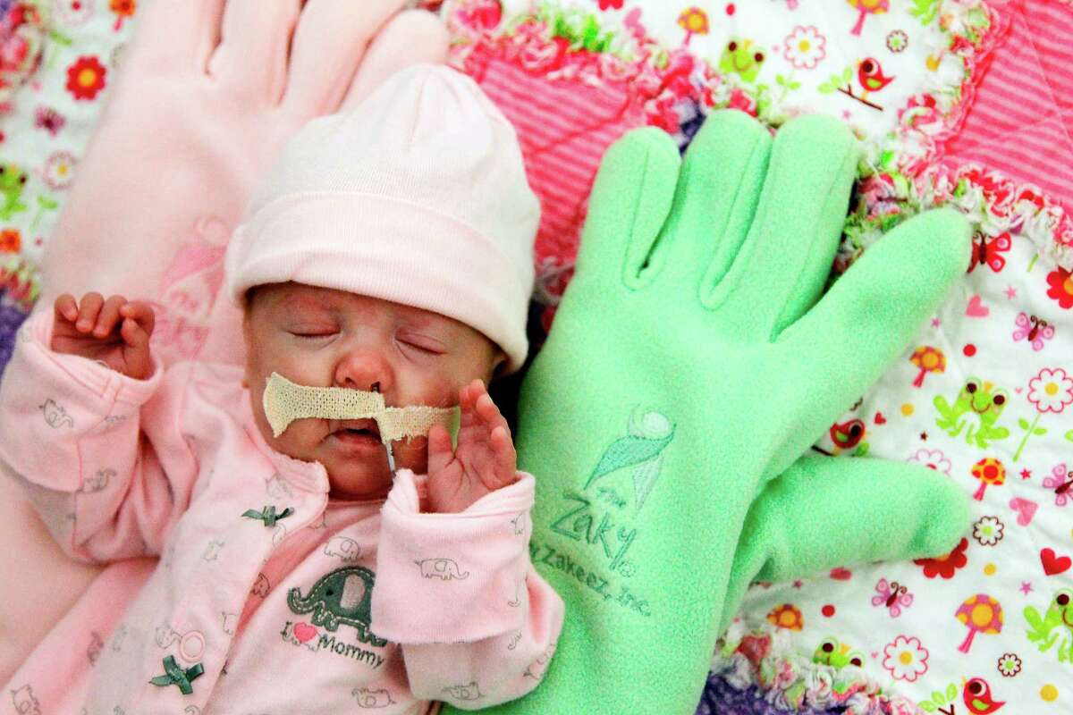 Trinity Osborne sleeps between two Zakys in the neonatal intensive care unit at Children's Memorial Hermann Hospital. Parents can leave their own scent on the fabric covering a Zaky by sleeping with it themselves before giving it to their child.