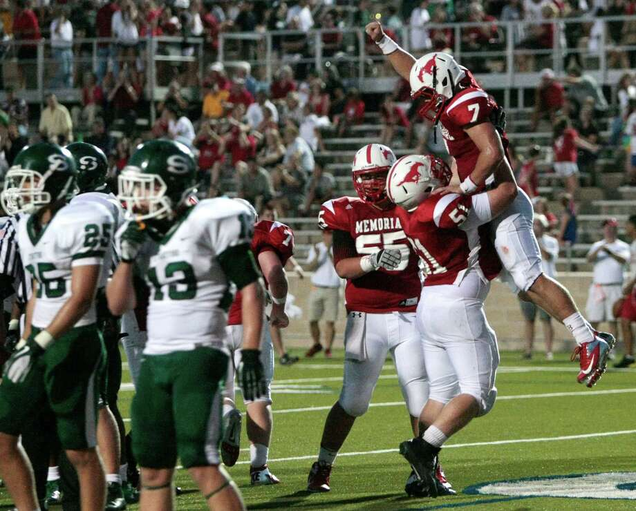 Memorial quarterback Tyler McCloskey (7) celebrates a touchdown with his offensive linemen Sherwood Hillyer (51) in the first half of Memorial High school and Stratford High school's match up at Tully Stadium Friday, August 31, 2012 in Houston, Texas. Photo: Billy Smith II, Houston Chronicle / © 2012 Houston Chronicle