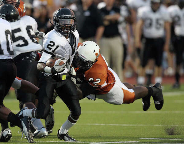 Steele's D'Angelo Wallace (21) evades a tackle by Madison's Vincent Taylor (92) in the first half at Heroes Stadium on Friday, August 31, 2012. Photo: Kin Man Hui, SAN ANTONIO EXPRESS-NEWS / ©2012 San Antonio Express-News