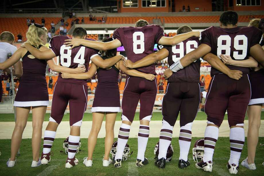 Cinco Ranch players and cheerleaders lock arms for the playing of the school song following a victory over Cy Ranch in a high school football game at BBVA Compass Stadium,Friday, Aug. 31, 2012, in Houston. Photo: Smiley N. Pool, Houston Chronicle / © 2012  Houston Chronicle