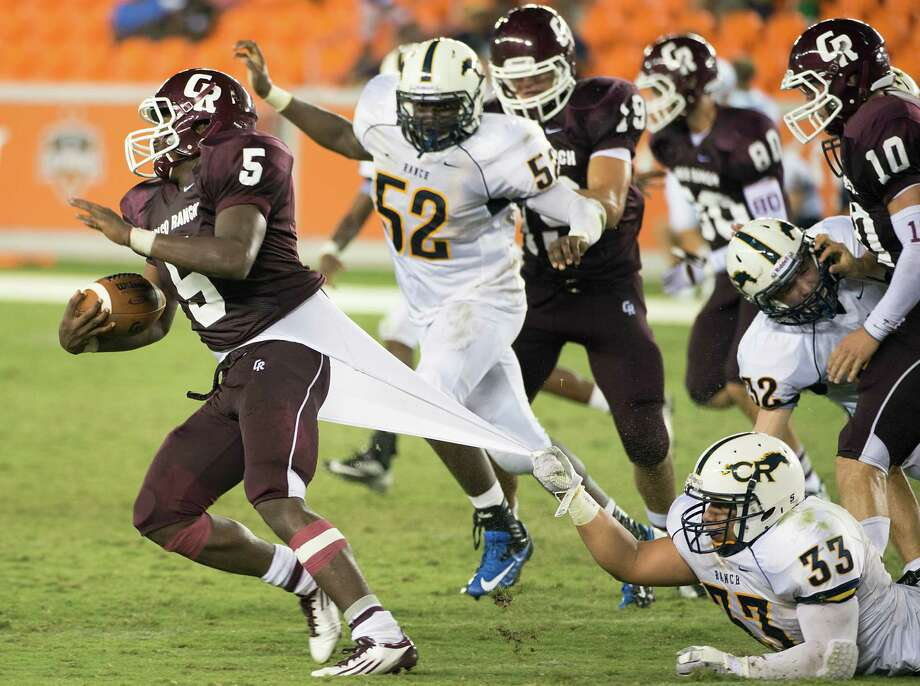 Cinco Ranch running back Denzelle Bates (5) slips away from Cy Ranch linebacker Ashton Ball (33) on an 84-yard run during the fourth quarter of a high school football game at BBVA Compass Stadium, Friday, Aug. 31, 2012, in Houston. Photo: Smiley N. Pool, Houston Chronicle / © 2012  Houston Chronicle