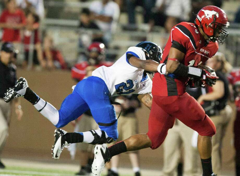 North Shore tight end Jacobie Russell (14) runs past Clear Springs Kamron Williams (21) at the Galena Park Athletic Complex on Friday, Aug. 31, 2012, in Houston. Photo: J. Patric Schneider, Houston Chronicle / © 2012 Houston Chronicle
