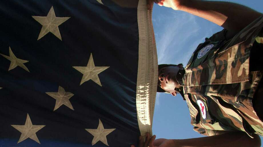 North Shore Junior ROTC member Andre Thomas folds the American flag before the match up against Clear Springs at Galena Park Athletic Complex on Friday, Aug. 31, 2012, in Houston. Photo: J. Patric Schneider, Houston Chronicle / © 2012 Houston Chronicle