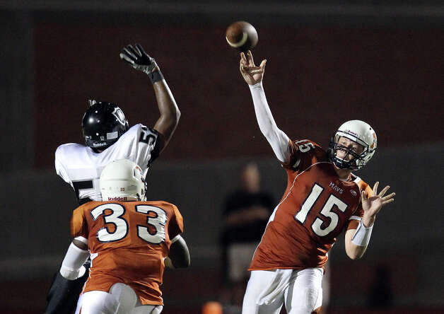 Madison quarterback Cody Ennis (15) attempts a pass over Steele's Matthew Simmons (52) in the second half at Heroes Stadium on Friday, August 31, 2012. Photo: Kin Man Hui, Express-News / ©2012 San Antonio Express-News